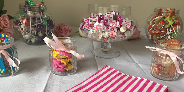 candy buffet table for a wedding, sweets in glass jars with pink ribbon
