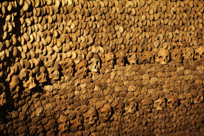 A photograph, taken in low artificial light, of rows of femurs end-on to the camera to form a wall, with one row of skulls about half-way up and another towards the bottom of the image.