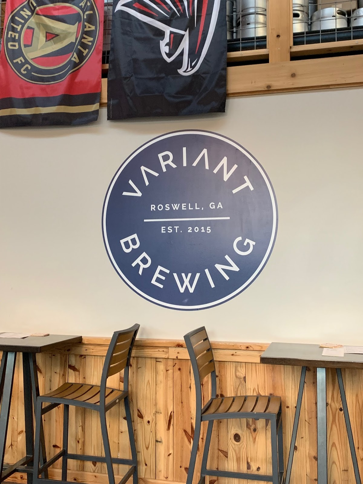 Some high top tables and chairs in front of the logo for Variant Brewing painted on the wall