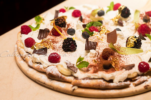 Chocolate flavoured Sweet Pizza with Banana, nuts, shaved chocolate, fresh berries & whipped cream.
