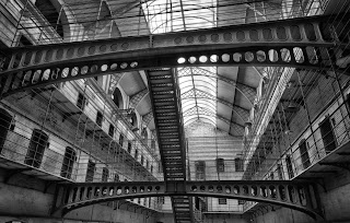 In black and white, a view of a Victorian prison wing from the ground floor looking up through tiers of cells and criss-crossing metal walkways to the glass roof.