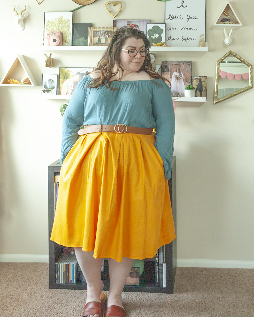 An outfit consisting of a Turkish blue off the shoulder blow with bell sleeves tucked into a yellow midi skirt and brown slide sandals.
