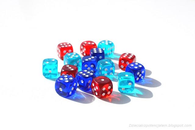 na zdjęciu piętnaście kostek w kolorach czerwonym, błękitnym i niebieskim leżących a środku stołu