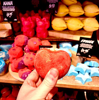 A bright red oval shaped bubble bar which looks like an apple with a oval green accessory on the top of it filled with some white butter on a background of brown rectangular shelves filled with different shaped and coloured bath bombs on a bright background