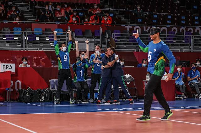 De azul, os jogadores brasileiros comemoram. O jogador Parazinho está em destaque na imagem, de camisa azul e calça preta fazendo gesto de número um para o banco de reservas, onde há três jogadores com os braços levantados em comemoração.