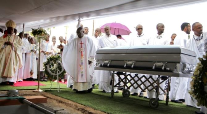 A priest gestures by the coffin of late King Kigeli V Ndahindurwa as relatives and friends attend the funeral service on January 15, 2017 in Nyanza. By Stephanie Aglietti (AFP)