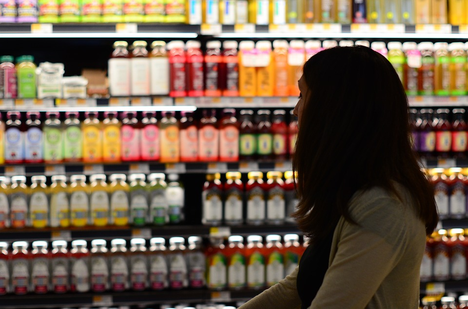 How to Stretch Your Food Dollars woman studying grocery store prices