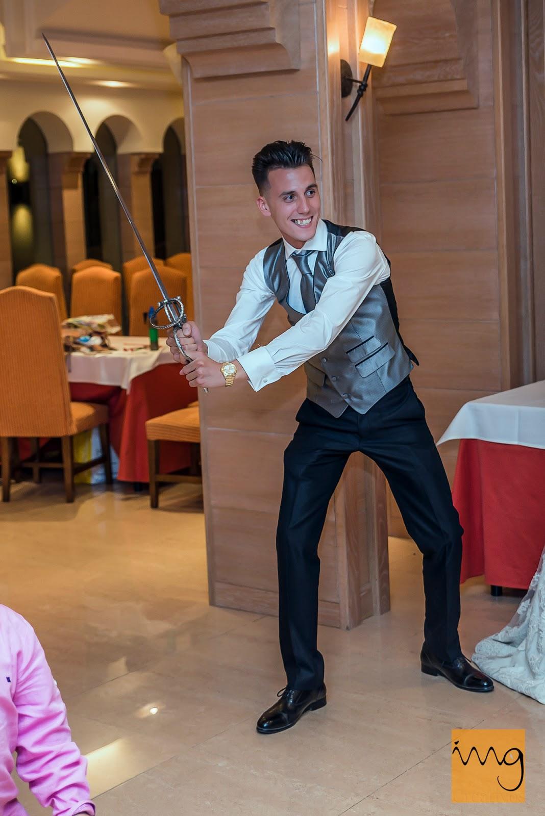 Fotografía divertida del novio con la espada para cortar la tarta de boda.