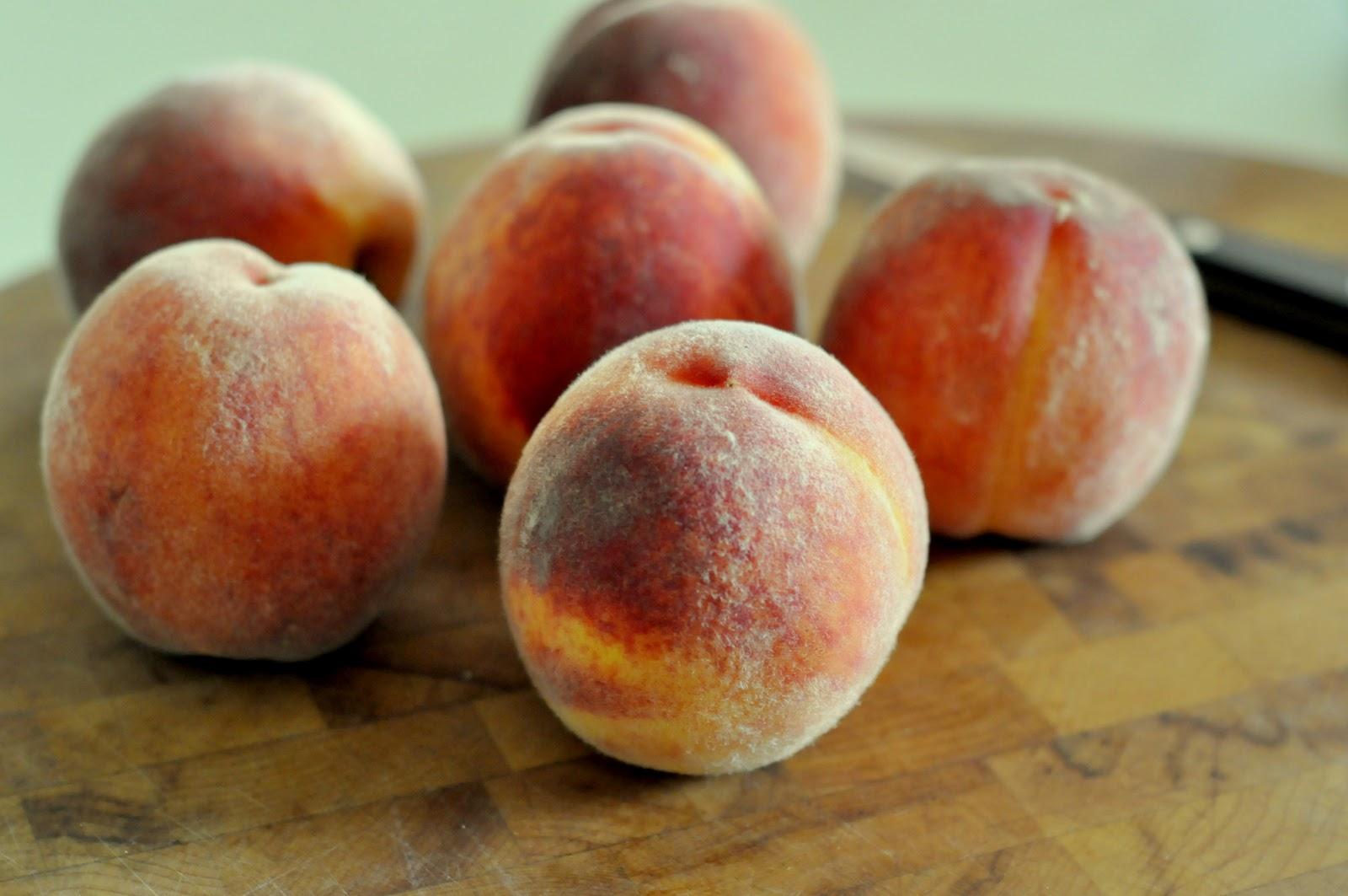 Bunch of fresh peaches sitting on a wooden cutting board   Taste As You Go