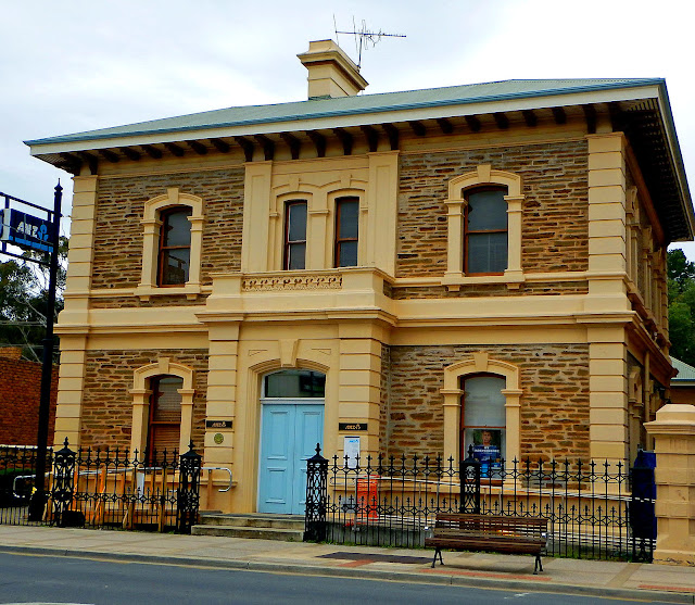 "ANZ Bank The Bank of Adelaide first opened a Gawler branch in 1866 and was responsible for the erection of this building in 1873. The cost of over 4,000 pounds made it one of the most expensive in Gawler. Writing in 1880 George Loyau described it as ""one of the chief ornaments of Murray Street"". The solid construction, spacious rooms and tall ceilings matched the image of a successful financial institution of the time. The effect of the 1890s depression on financial institutions can be gauged from the decision in to close the bank's Gawler branch and the building was sold to the Freemasons for 1125 pounds. The building was later repurchased by the Bank of Adelaide and when the bank was sold because of financial difficulties in 198? it became the premises of the ANZ Bank (check this). A well designed rear extension was opened in 19?? featuring an interesting glass feature wall. The magnificent cast iron fence and gates were made at the Phoenix Foundry of James Martin, the largest of the Gawler foundries which at its peak employed over 700 workers. The bluestone for this and many other major Gawler buildings was quarried from the Gawler South hills. State Heritage Register"