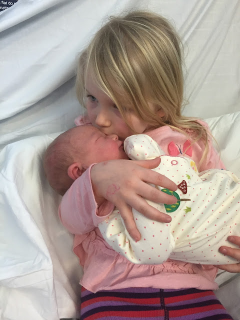 A big sister holds her baby sister for the first time