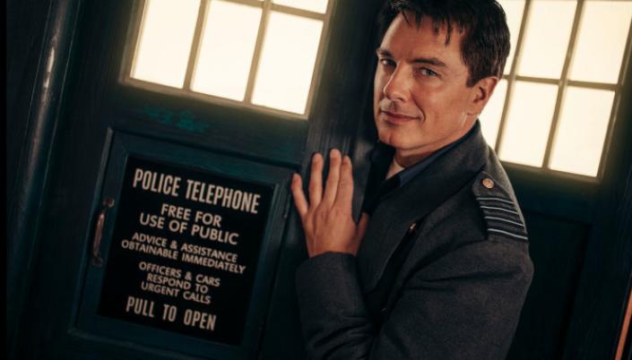 Imagem: Jack. Homem branco de meia idade. Cabelo curto preto e grisalho. Tem olhos azuis e sorri com malicia. Usa sobretudo cinza e está na frente de uma cabine telefônica da polícia.