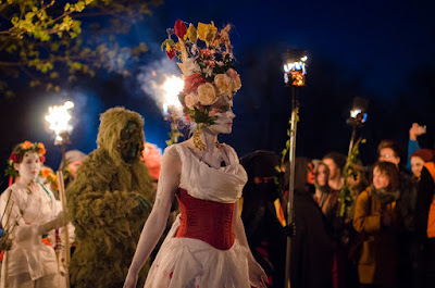 A woman in a white dress and a flower crown. There is a man in a green costume behind her. It's the May Queen and theGreen Man at the Beltane Fire Festival in Edinburgh, Scotland.