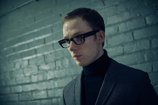 Joe Cole as Harry Palmer in a black turtleneck sweater and black rimmed spectacles