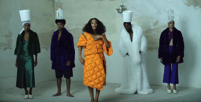 Solange standing front and center of a group of men and women