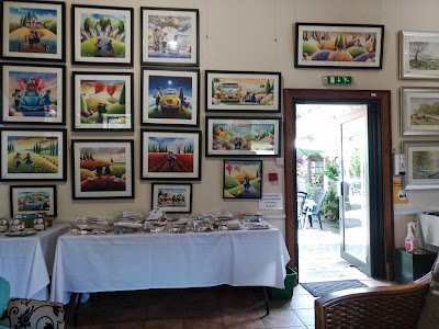 A wall of framed pictures, painted in very bright colours, almost childlike.
