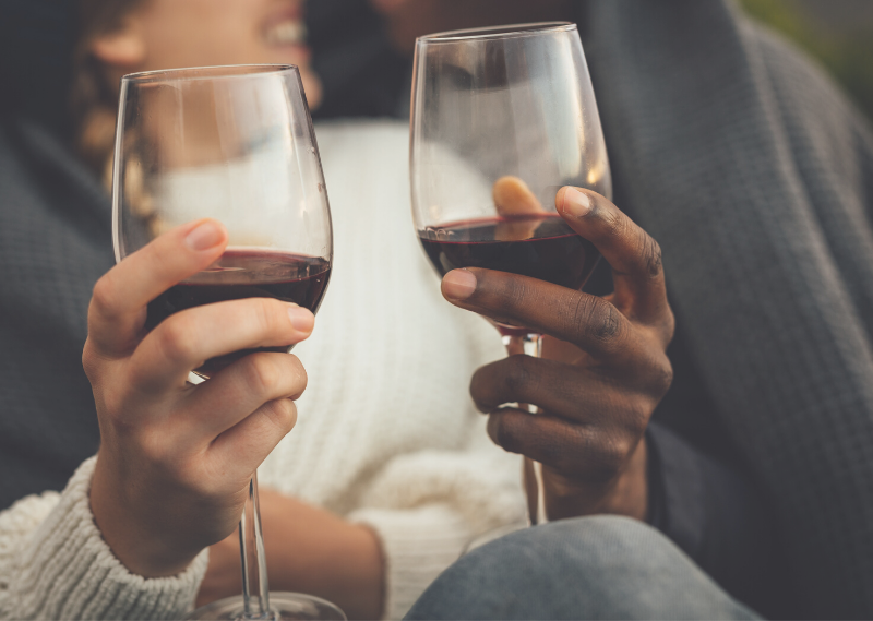 A couple holding glasses of red wine in a blog post about simple ways to create lasting memories with your partner.