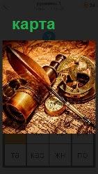 на столе лежат карта  с подзорной трубой и компас с гусиным пером