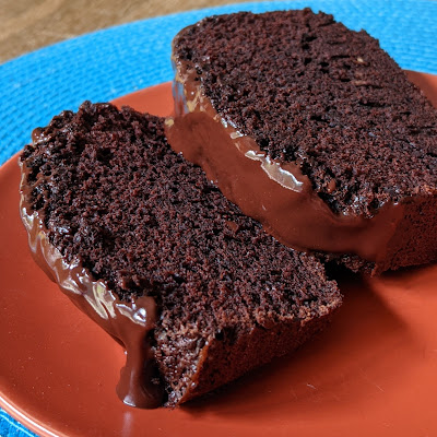 two slices of loaf, dripping chocolate glaze on a pumpkin colored plate on a turquoise placemat