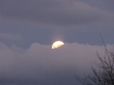 full moon behind clouds