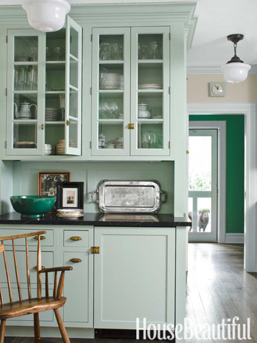 These sleek black countertops paired with turquoise cabinets give this farmhouse kitchen a fun retro feel