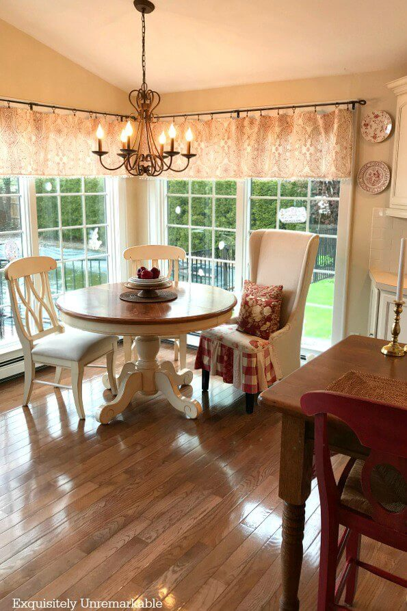 Cute Cottage Style Kitchen nook with round table and red accents