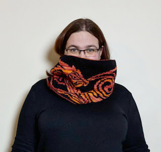 A person with dark hair and glasses facing the camera wearing a black shirt and an orange and pink patterned black shawl.