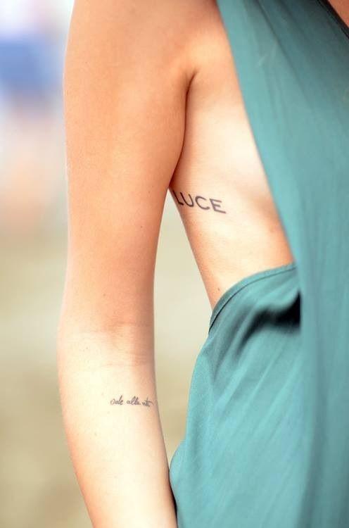 chica va vestida de verde, lleva un tatuaje muy sexy junto al pecho , es un tatuaje de letras