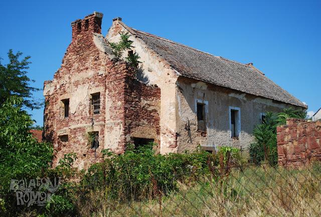 Romos zsinagógaépület kővágóörsön, balra a női karzat külső feljárata. Lemállott vakolatú téglafalak.