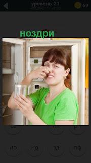 девушка открыла холодильник и зажала ноздри от запаха