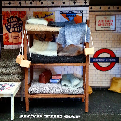 Miniature scene of a three-tier bunk in an underground shelter set up in a 1940s tube station.