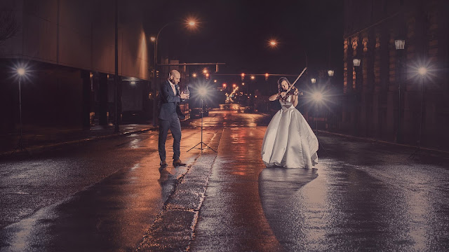 a backlit man takes photos of his wife on their wedding day while she plays the violin