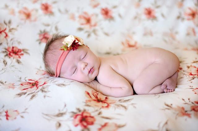 newborn girl on floor blanket