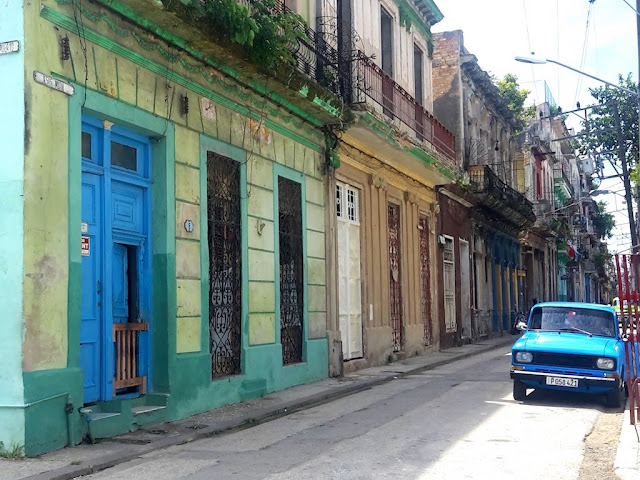 Brightly colored Cuban street and vintage car