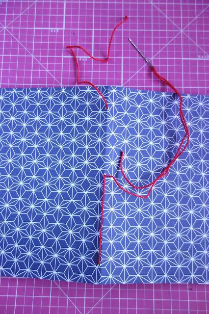 self-healing mat, scrapbook paper, needle, thread