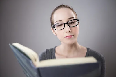 Women in glasses reading a book