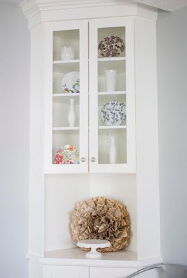 Small white built-in dining room hutch with glass doors