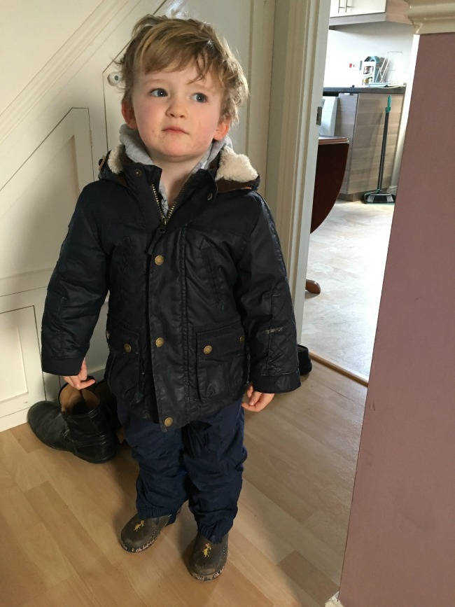 our-weekly-journal-27-march-toddler-dressed-in-waterproofs-and-wellies-standing-in-the-hallway-waiting-to-go-out