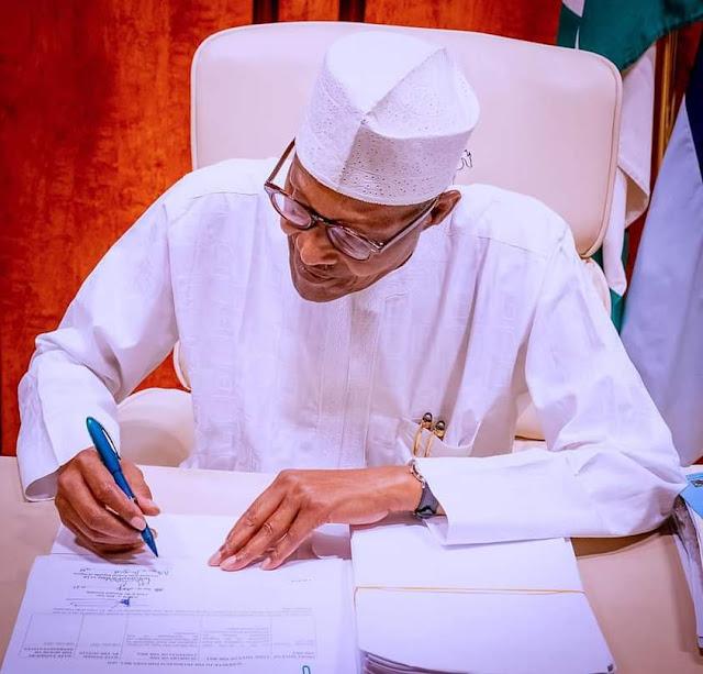 "Alt: = ""President Buhari signing document"""