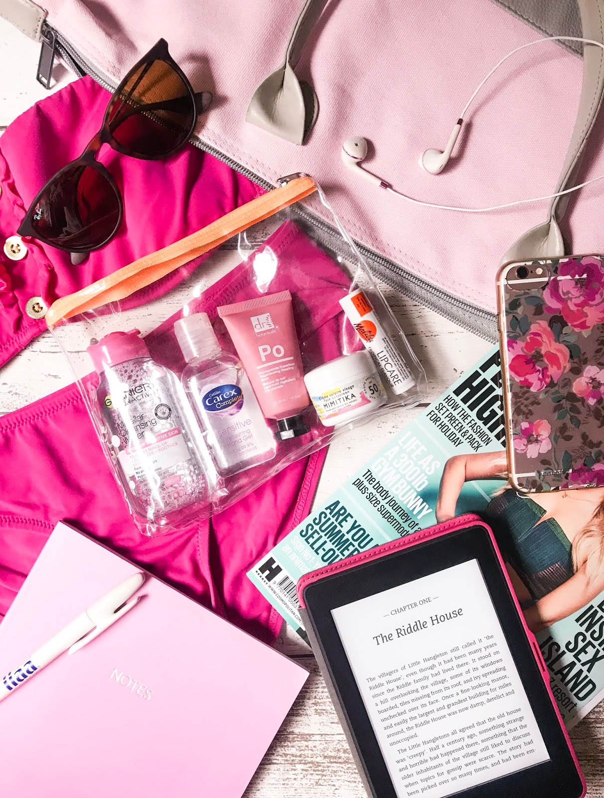 hand luggage items sunglasses, kindle, notebooks and beauty products