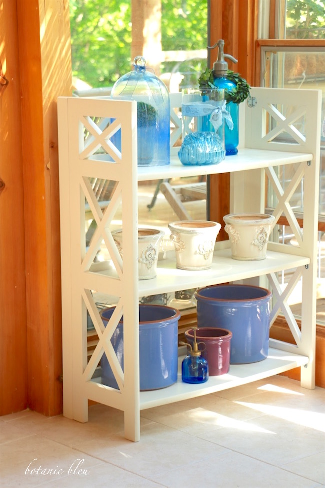 white-shelves-with-blue-glass-bottles-and-pots