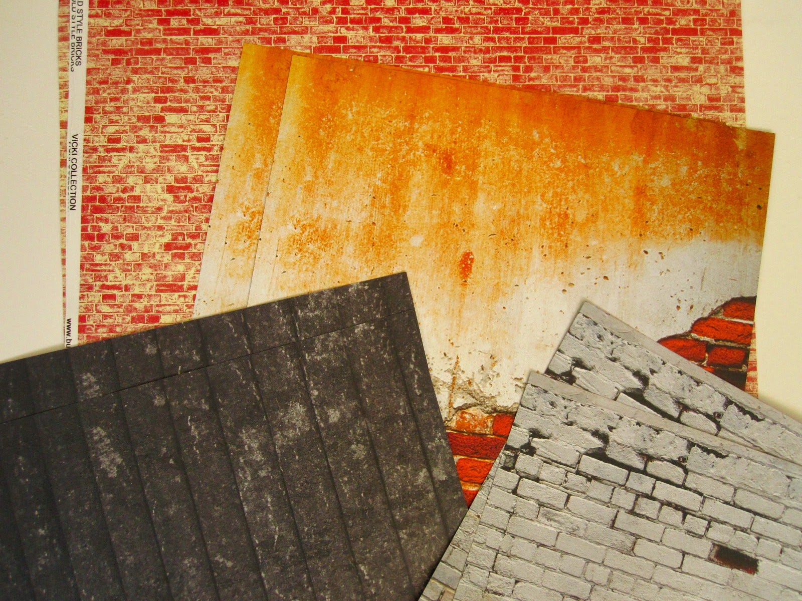 A selection of scrapbook paper sheets with distressed brick, plaster and wood patterns.