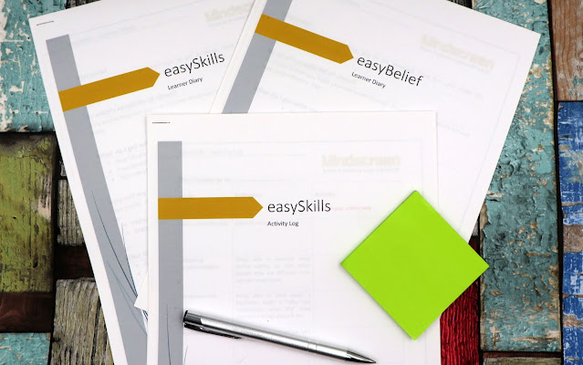 A flatlay of a selection of A4 handouts from the Mindscreen Experience program, with a pen and some green post its