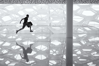 A man runs with a briefcase through a white room