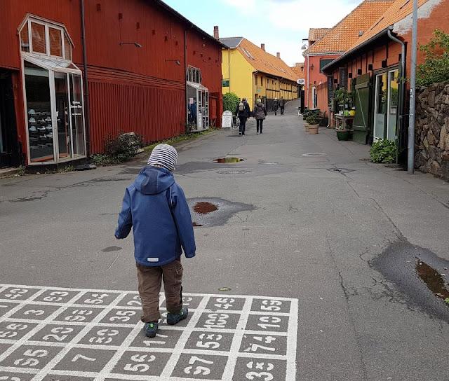 Bornholm mit Kindern im Herbst. Teil 3: 10 tolle Ausflugsziele für Familien auf Dänemarks Sonneninsel. Das Hühnerbingo in Svaneke wird vom Kind als Hüpfekästchen genutzt.