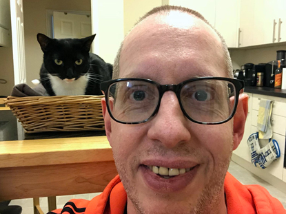man wearing glasses with black and white cat sat in a basket behind him