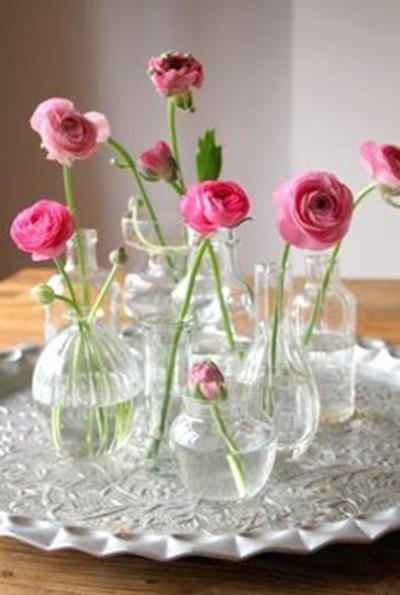 Satu nampan berisi vas bunga dari botol kaca bekas