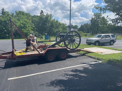 Artillery carriage sitting on the back of a flatbed trailer, ready to be placed on its new concrete pad in the parking lot median