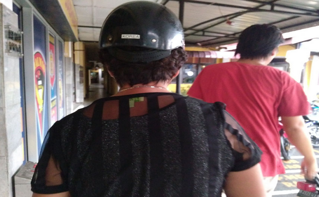 A Lien (pakai helm) saat memasuki Mapolres Pematangsiantar untuk membuat laporan pengaduan.