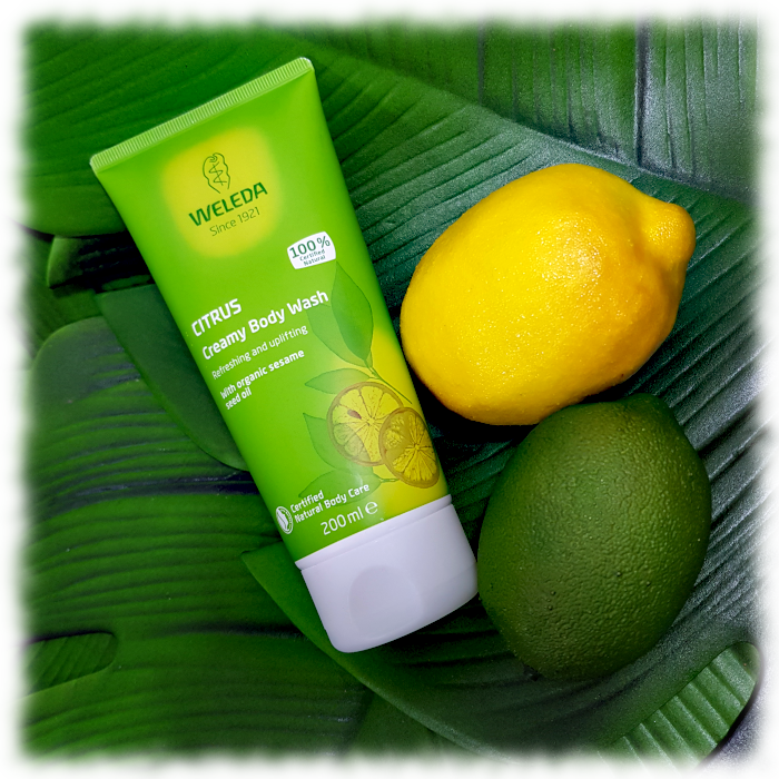 Weleda Citrus Creamy Body wash pictured with a lemon & a lime